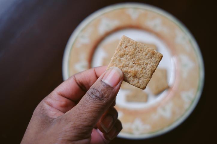 Woman Snacks on Whole Grain Crackers