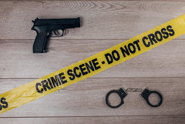 Crime scene tape, handcuffs and gun on wooden background