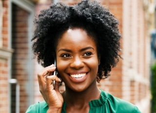 Woman on smart phone, smiling - stock photo