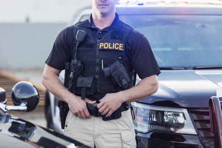 Policeman wearing bulletproof vest, by patrol car