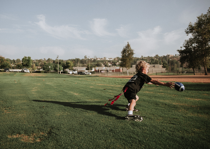 Boy playing flag football catching a ball, California, United States
