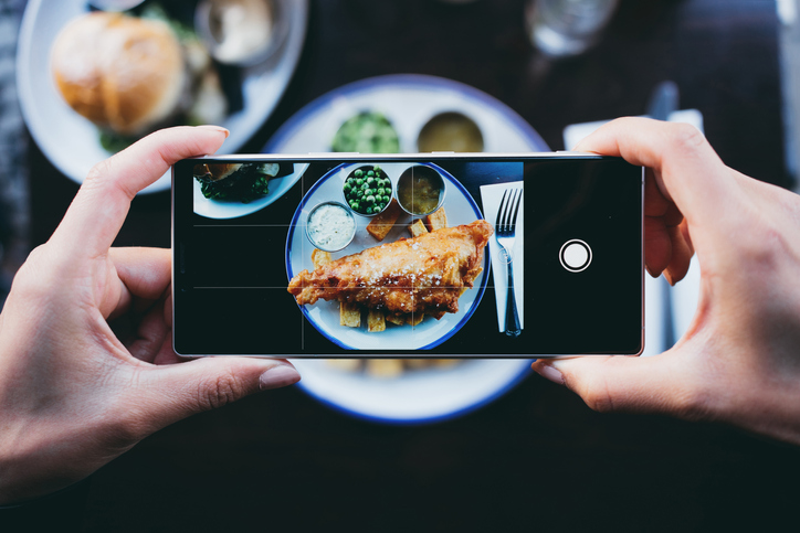 Woman photographing fish and chips in a restaurant with a smartphone