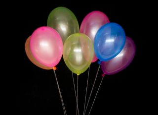 Multi Colored Balloons Tied With White Thread On Black Background