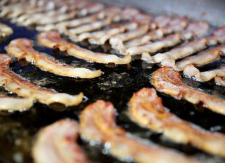 Bacon at the Hatfield Quality Meats stand cooks on the griddle during the Pennsylvania Farm Show on Friday Jan. 16, 2015. Photo by Natalie Kolb 1/16/15