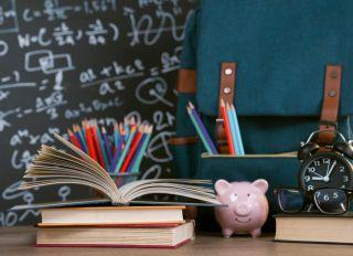 Back to school: multicolored school supplies shot on wooden desk