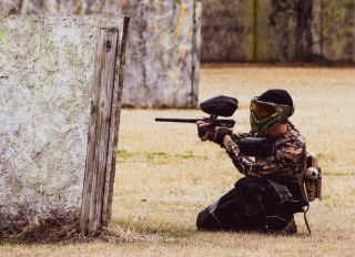 Man Crouching With A Paintball Gun
