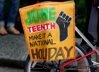 Demonstrators Protest With Juneteenth Sign