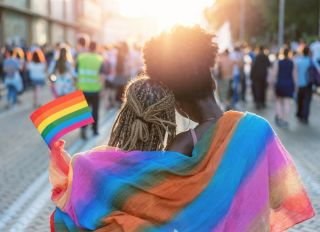 Young female couple hugging with rainbow scarf at the pride event