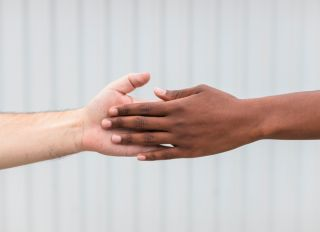 Woman and man touching hands by white wall