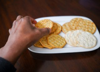 Woman Snacks on Crackers