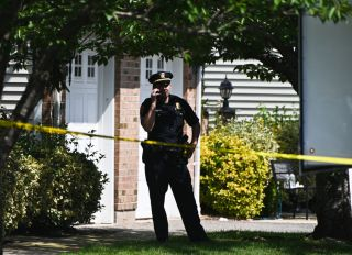 Suffolk County, New York policeman stands in front of crime scene on Long Island