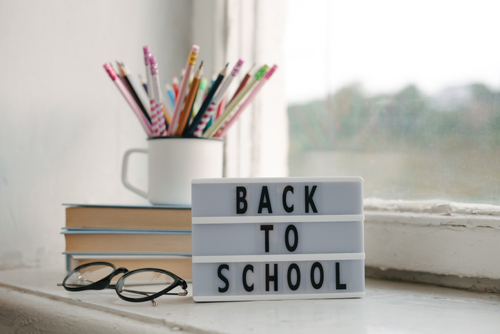 Books, pencils, eyeglasses and earphones on window sill. School, learning concept. White lightbox with text Back to School.