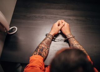 Tattooed male prisoner with handcuffs sitting in prison visit room