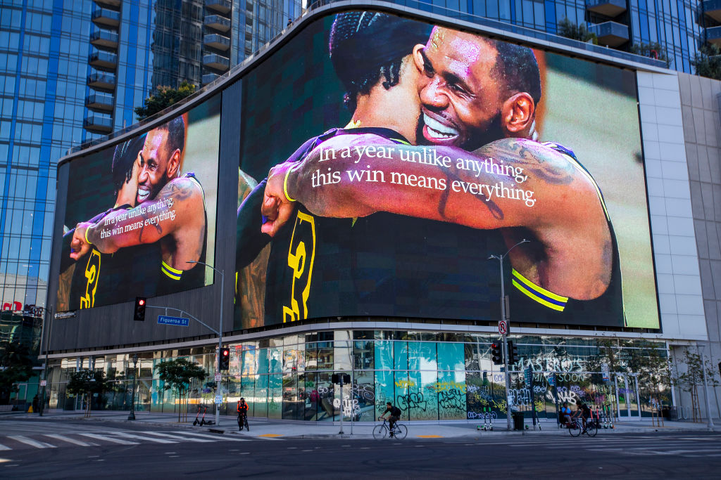 Graffiti remains on the windows below as people pass underneath giant video screens featuring Lakers champions LeBron James and Anthony Davis hugging at the Circa apartment complex across the street from the Staples Center...