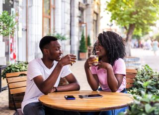 Portrait of stylish black couple at summer street cafe.