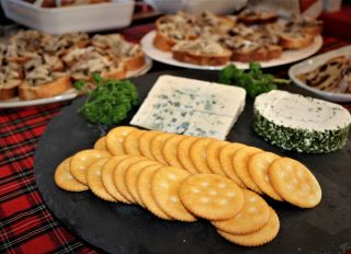Close-Up Of Buffet Food With Cheese And Biscuits In Foreground