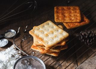 Square Dry Crackers Biscuit On A Wooden Table. Wooden Texture Dark Background. Snack Dry Biscuits